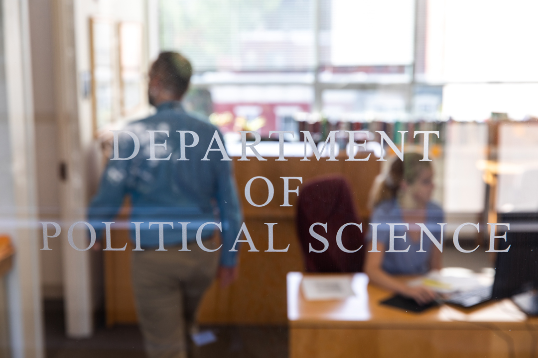 Department of Political Science sign on a glass door with a man and woman in the office in the background